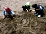 Students build Borobudur-like sandcastles on the beach.