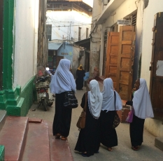 School children of all ages and sporting a variety of uniforms spill out onto the narrow labyrinthine streets of Stone Town.