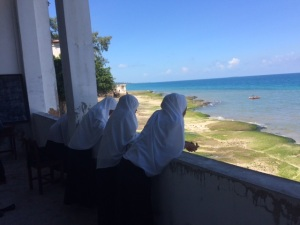 Students at the Tumekuja School use their break to gaze out at the Indian Ocean, a challenge to some teachers who have to speak loudly to compete with the sounds of the sea.